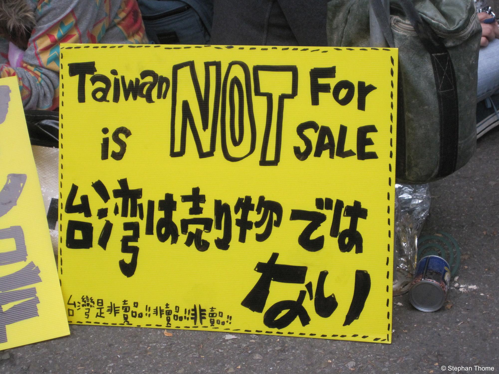 Protest in drei Sprachen: Englisch, Japanisch, Chinesisch.